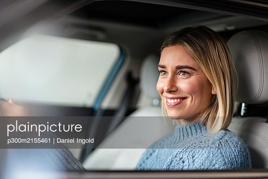 Portrait of smiling young woman driving a car - p300m2155461 by Daniel Ingold
