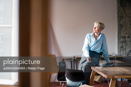 Smiling businesswoman with laptop sitting on desk while looking away at home office - p300m2266953 by Robijn Page
