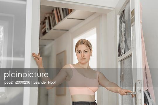 Blond woman posing next door - p552m2090236 by Leander Hopf