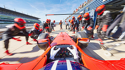 Pit crew ready for formula one race car in pit stop - p1023m1443900 by Chris Ryan