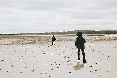 Two brothers running along empty beach - p1166m2130493 by Cavan Images