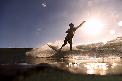 Surfer on a wave at sunset time - p1166m2137474 by Cavan Images