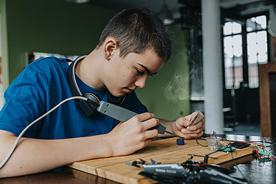 Boy sitting at home using soldering iron - p300m2214101 by Mareen Fischinger