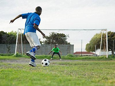 Teenage boys playing football - p9246611f by Image Source