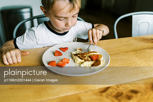 Little boy eating a pancake with fresh strawberries at home - p1166m2201444 by Cavan Images