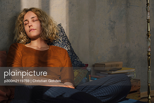 Portrait of student sitting on bed relaxing - p300m2119759 by Christian Gohdes