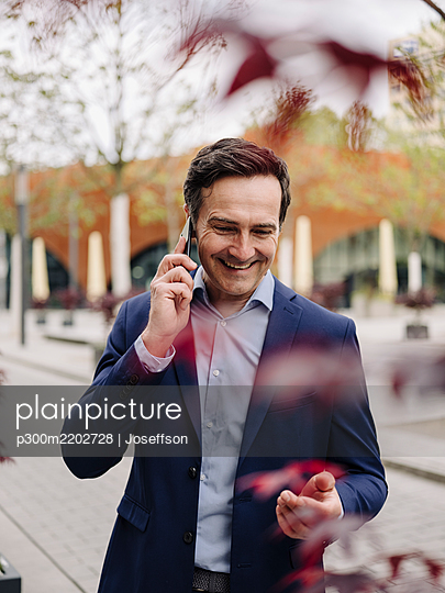 Happy mature businessman on the phone in the city - p300m2202728 by Joseffson