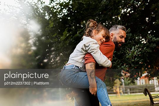 Father giving daughter piggyback ride - p312m2237302 by Plattform