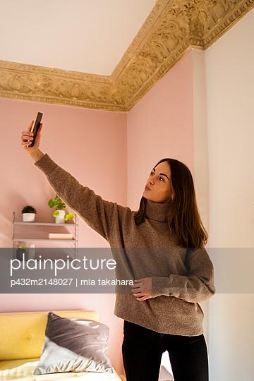 Junge Frau macht Selfie - p432m2148027 von mia takahara
