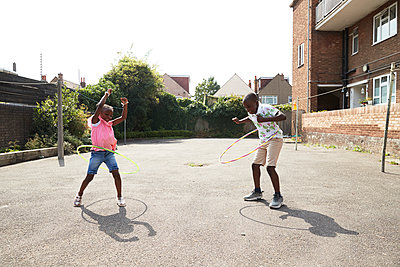 Playful brother and sister spinning in plastic hoops in sunny lot - p1023m2238498 by Himalayan Pics