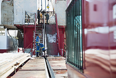 Workers on drilling rig at gas plant - p1192m1128014f by Hero Images