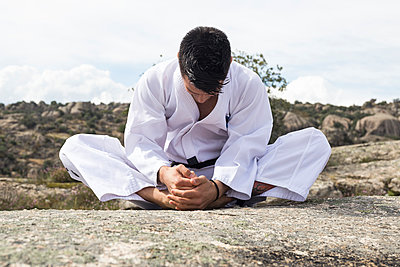 Man stretching before a martial arts training - p300m1469633 by Andrés Benitez