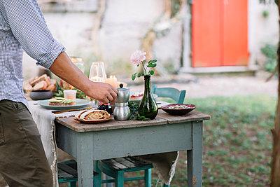 Close-up of man taking moka pot from garden table - p300m2068355 von Alberto Bogo