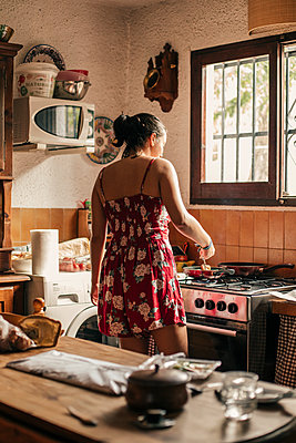 Rear view of woman cooking in kitchen using a pan - p300m2131662 von Aitor Carrera Porté