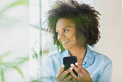 Smiling woman with mobile phone looking through window at home - p300m2276416 by Steve Brookland