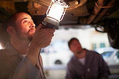 Two car mechanics at work in repair garage - p300m975574f by zerocreatives