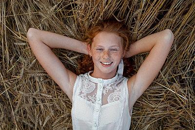 Caucasian girl laying in wheat - p555m1521602 by Vyacheslav Chistyakov