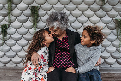 Portrait of grandmother sitting close with twin grandchildren - p1166m2163416 by Cavan Images