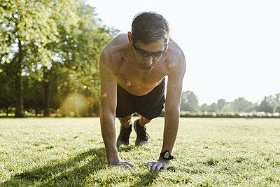 Man doing push ups outside - p1166m2190831 by Cavan Images