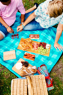 High angle view of male friends having cherries during picnic at park - p1264m1089270f by Astrakan