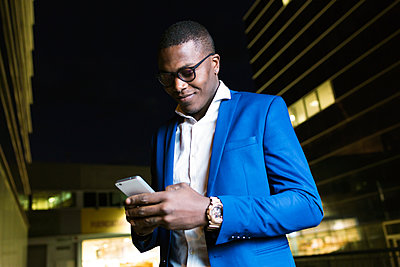 Young businessman wearing blue suit jacket and using smartphone at night - p300m2114584 by Josep Suria