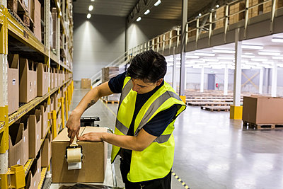 Young male worker packing cardboard box with adhesive tape at distribution warehouse - p426m2018879 by Maskot