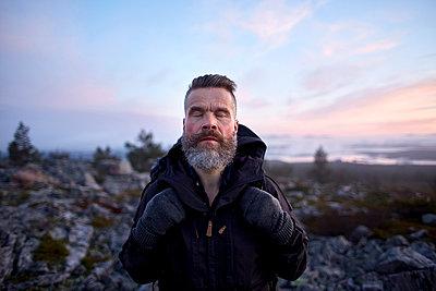 Hiker enjoying nature with eyes closed, Sarkitunturi, Lapland, Finland - p429m1188017 by Aleksi Koskinen