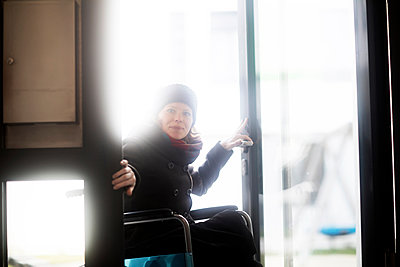 Woman in wheelchair entering building - p429m2069284 by Sigrid Gombert