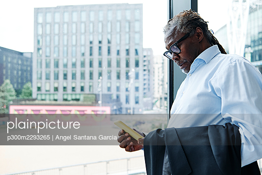 Senior male professional using smart phone while leaning on glass wall - p300m2293265 by Angel Santana Garcia