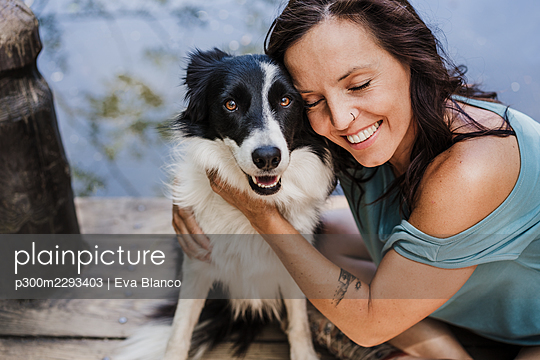 Smiling woman with eyes closed hugging pet dog while sitting on pier - p300m2293403 by Eva Blanco