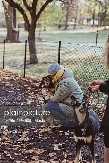 Side view of man crouching while embracing dog at park - p426m2194809 by Maskot