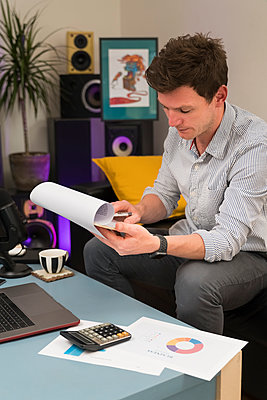 Businessman reading document while sitting at home office - p300m2250806 by Boy photography