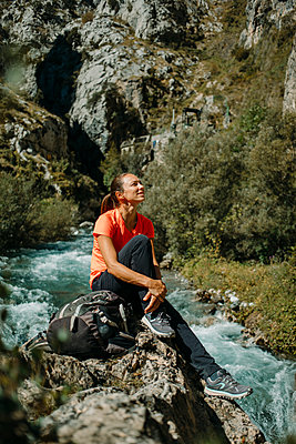 Mid adult woman looking away while sitting by river at Cares Trail in Picos De Europe National Park, Asturias, Spain - p300m2250831 by David Molina Grande