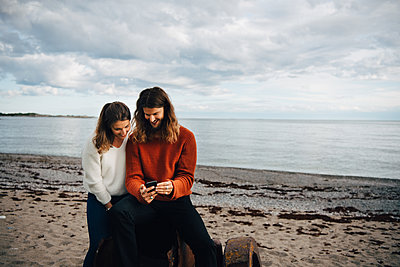 Smiling man showing mobile phone to woman while sitting at beach - p426m2149224 by Maskot