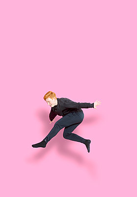 Jumping girl in front of pink background - p427m2272306 by Ralf Mohr