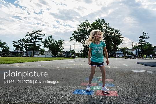 Girl playing hopscotch on blacktop in suburbs - p1166m2112736 by Cavan Images