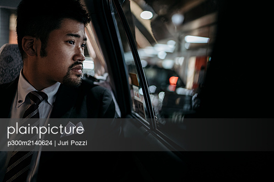 Young businessman in a taxi looking out of window - p300m2140624 by Juri Pozzi