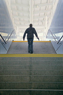 Man walking up steps holding a gun - p1072m829399 by Neville Mountford-Hoare