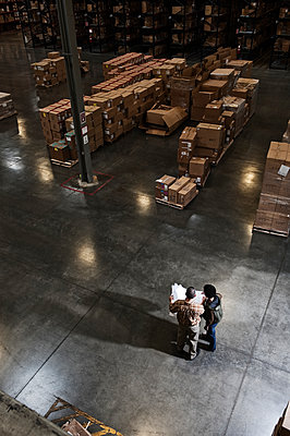 Two warehouse workers going over inventory sheets of products in a distribution warehouse. - p1100m2002282 by Mint Images