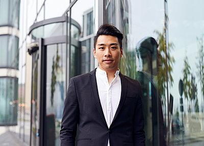 Asiatischer Mann lehnt an Scheibe - p1124m1181512 von Willing-Holtz