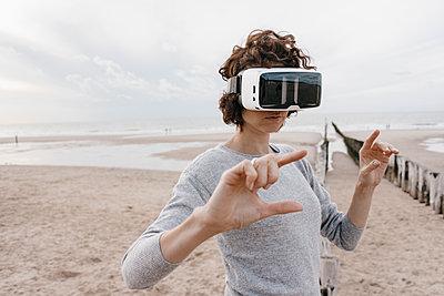Woman on the beach wearing VR glasses - p300m1499457 by Kniel Synnatzschke