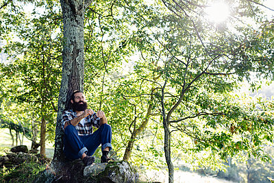 Man with beard relaxing at tree trunk in the forest - p300m2140974 by Sofie Delauw