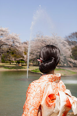 Young woman in orange kimono watching fountain in sunny Spring park - p301m2271992 by Sven Hagolani