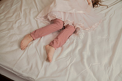 Little girl, covered up, on her bed - p397m1083272 by Peter Glass