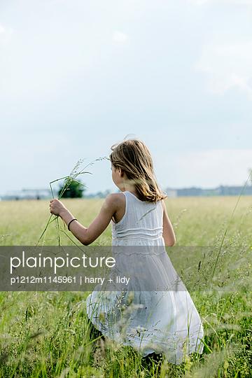 Mädchen im weißen Kleid pflückt Blumen - p1212m1145961 von harry + lidy
