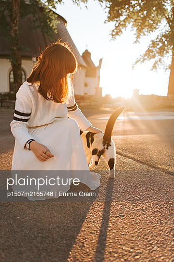 Petting my cat in the sunset - p1507m2165748 by Emma Grann