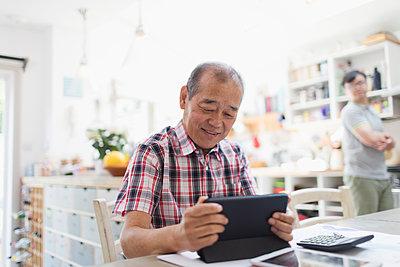 Senior man using digital tablet in kitchen - p1023m2033847 by Sam Edwards