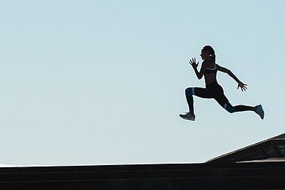 Silhouette of female athlete jumping against blue sky - p1166m2136154 by Cavan Images