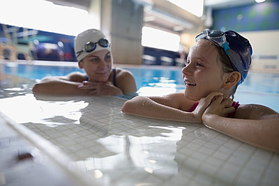 Mother and daughter swimmers bonding at edge of swimming pool - p1192m1447632 by Hero Images