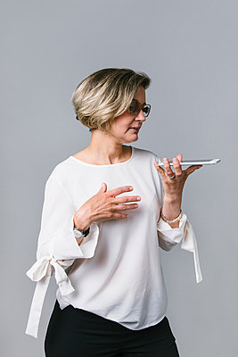 Businesswoman with smart phone talking on speaker phone - p1192m2123258 by Hero Images